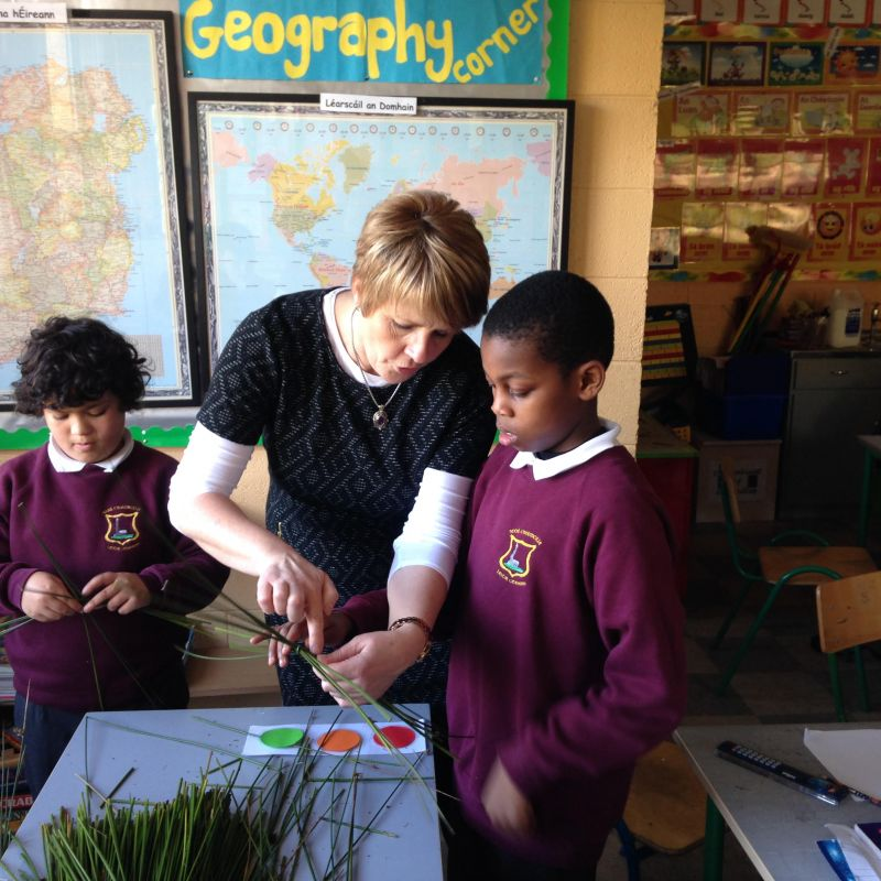 Mrs. Doherty helping the boys make St. Brigid's crosses